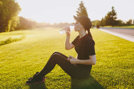 Young girl in black uniform, cap sitting relaxing resting on green lawn after sport exercises, running, drinking water from bottle on outdoors on sunny summer day. Fitness, healthy lifestyle concept Stock Photo