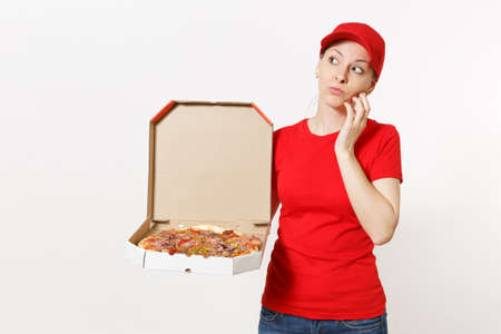 Delivery woman in red uniform isolated on white background. Pretty female in cap, t-shirt, jeans working as courier or dealer holding italian pizza in cardboard flatbox. Copy space for advertisement