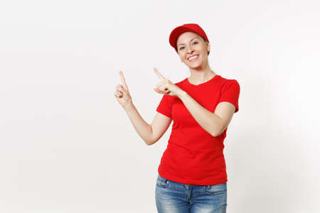 Delivery woman in red uniform isolated on white background. Professional caucasian female in cap, t-shirt, jeans working as courier or dealer, pointing index fingers aside, copy space advertisement