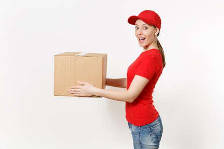 Kobieta dostawy w czerwonym mundurze na białym tle. Kobieta w czapce, t-shircie, dżinsach, pracująca jako kurier lub sprzedawca, trzymając karton. Otrzymanie paczki. Skopiuj reklamę przestrzeni. Widok z boku