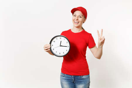 Delivery woman in red uniform isolated on white background. Professional female in cap, t-shirt, jeans working as courier or dealer, holding round clock, showing in time. Copy space for advertisement
