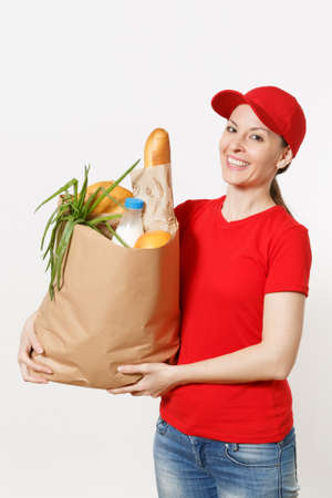 Delivery woman in red uniform isolated on white background. Female courier in cap, t-shirt, jeans holding paper packet with food. Products delivery from shop or restaurant to your home. Copy space