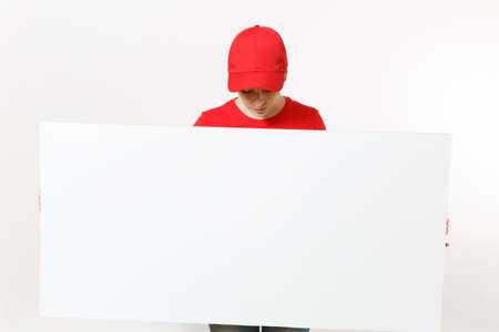 Delivery woman in red uniform isolated on white background. Female courier in cap, t-shirt, jeans holding big white empty billboard. Copy space advertisement. Place for text, image. Advertising area