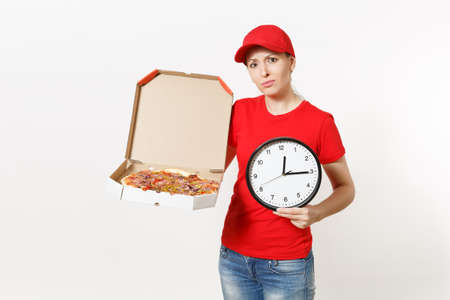 Delivery woman in red uniform isolated on white background. Pretty female in cap, t-shirt, jeans working as courier holding italian pizza in cardboard flatbox and clock. Copy space for advertisement