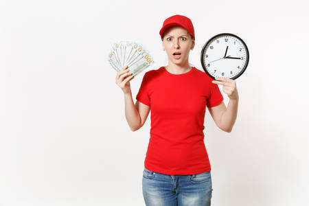 Delivery woman in red uniform isolated on white background. Shocked female in cap, t-shirt, jeans working as courier or dealer, holding bundle odollars cash money clock. Copy space for advertisement Stok Fotoğraf