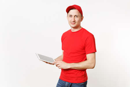 Delivery man in red uniform isolated on white background. Male in cap, t-shirt, jeans working as courier or dealer, holding tablet pc computer with blank empty screen. Copy space for advertisement