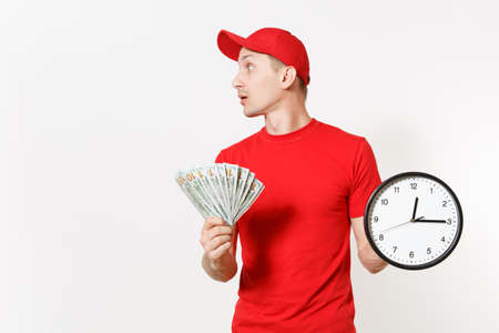 Delivery man in red uniform isolated on white background. Smiling male in cap, t-shirt, jeans working as courier or dealer, holding bundle of dollars cash money, clock. Copy space for advertisement