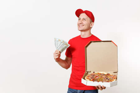 Delivery man in red uniform isolated on white background. Male in cap, t-shirt working as courier holding italian pizza in cardboard flatbox, bundle of dollars, cash money. Copy space advertisement