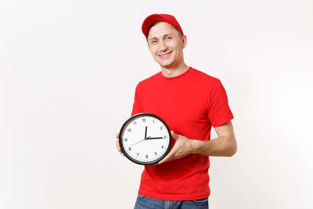 Delivery man in red uniform isolated on white background. Professional male in cap, t-shirt, jeans working as courier or dealer, holding round clock, showing in time. Copy space for advertisement