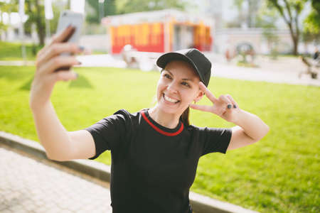 Young athletic smiling beautiful brunette girl in black uniform and cap doing selfie on mobile phone during training, showing victory sign, standing in city park outdoors. Fitness, healthy lifestyle