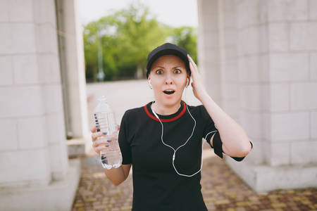 Young athletic shocked beautiful brunette girl in black uniform and cap with headphones holding bottle with water, listening music spreading hands in city park outdoors. Fitness, healthy lifestyle Stock Photo - 103466645