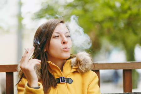 Beautiful happy caucasian young smiling brown-hair woman in yellow coat smoking cigarette in outdoor restaurant or cafe in autumn season. Rest, smoke, relax