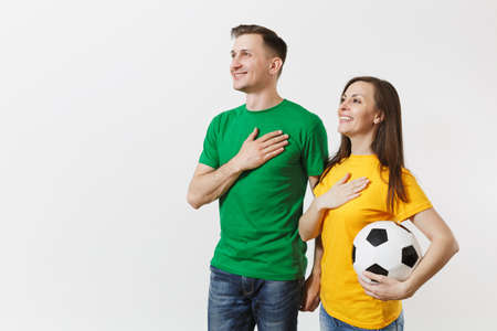 Emotional couple, woman man, football fans in yellow green t-shirt cheer up support team with soccer ball singing national country anthem isolated on white background. Sport leisure lifestyle concept Stock Photo