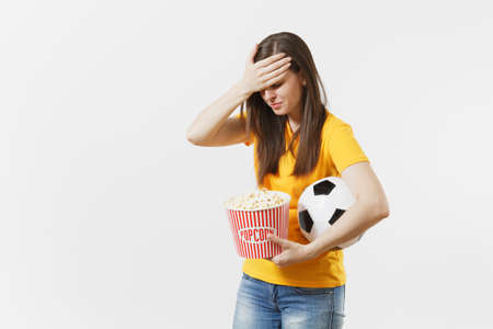 Screaming European woman, football fan holding soccer ball, bucket of popcorn upset of loss or goal of favorite team isolated on white background. Sport, play football, cheer, fans lifestyle concept