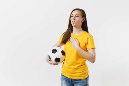 European woman, football fan in yellow uniform holding soccer ball, singing national country anthem isolated on white background. Sport, play football, cheer, fans people support, lifestyle concept