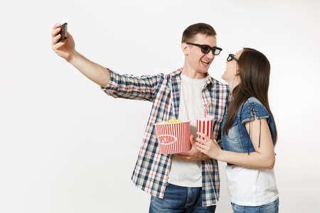 Young couple, woman and man in 3d glasses watching movie film on date, holding bucket of popcorn and cup of soda or cola, doing selfie on mobile phone isolated on white background. Emotions in cinema