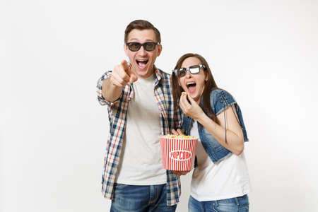 Young happy laughing couple, woman and man in 3d glasses and casual clothes watching movie film on date, holding bucket and eating popcorn isolated on white background. Emotions in cinema concept