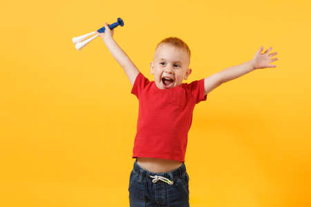Little cute kid baby boy 3-4 years old, football fan in red t-shirt holding in hand pipe, blowing isolated on yellow background. Kids sport family leisure lifestyle concept. Copy space advertisement