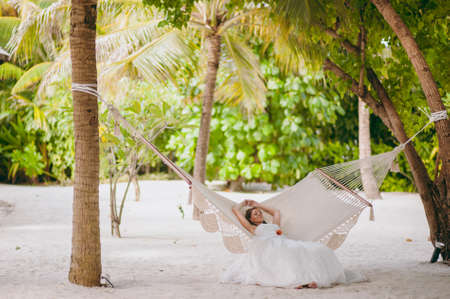 The beautiful bride lies on a hammock on the beach Stock Photo