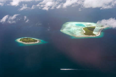 The tropical islands and atolls in Maldives in Indian Ocean from aerial view. Cutting wave boat. Piece of paradise on the Earth. Good choice for vacation. Beautiful top view for wallpaper.