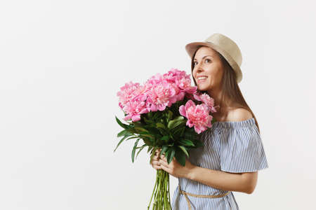 Young tender woman in blue dress, hat holding bouquet of beautiful pink peonies flowers isolated on white background. St. Valentine's Day, International Women's Day holiday concept. Advertising area