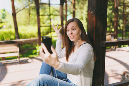 Portrait of beautiful woman wearing light casual clothes. Smiling female sitting in city park in street outdoors on spring nature, doing selfie shot on mobile phone or video call. Lifestyle concept