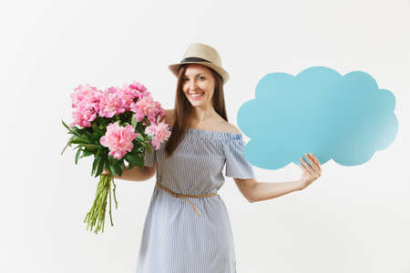 Young woman in blue dress, hat holding blank empty say cloud, speech bubble with place text, bouquet of pink peonies flowers isolated on white background. Holiday concept. Advertising area copy space Banco de Imagens
