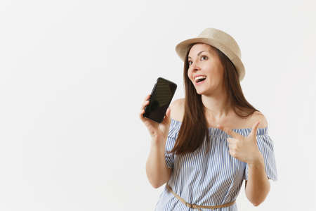 Young woman dressed blue dress, hat showing to camera mobile phone with blank black empty screen isolated on white background. People sincere emotions, lifestyle concept. Advertising area. Copy space