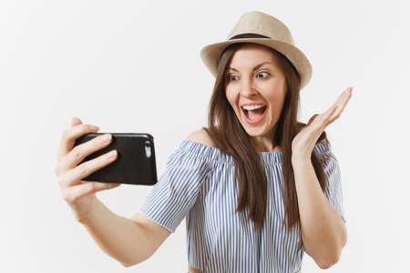Young beautiful woman dressed blue dress, hat doing selfie shot on mobile phone or video call isolated on white background. People, sincere emotions, lifestyle concept. Advertising area. Copy space Banco de Imagens