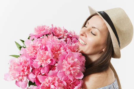 Young tender woman in blue dress, hat holding bouquet of beautiful pink peonies flowers isolated on white background. St. Valentines Day, International Womens Day holiday concept. Advertising area