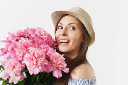 Close up young tender woman in blue dress, hat holding bouquet of pink peonies flowers isolated on white background. St. Valentine's Day, International Women's Day holiday concept. Advertising area Banco de Imagens