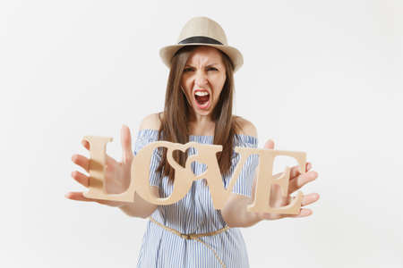 Mad wild crazy screaming woman holding wooden word love isolated on white background. St. Valentine's, International Women's Day holiday. People, sincere emotions, lifestyle concept. Advertising area