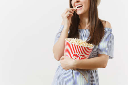 Cropped photo woman in blue dress, hat watching movie film eating popcorn from bucket isolated on white background. People, sincere emotions in cinema, lifestyle concept. Advertising area. Copy space Banco de Imagens