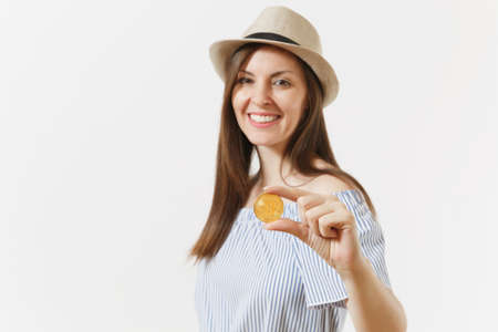 Young elegant woman in blue dress, hat with long hair holding bitcoin coin of golden color isolated on white background. People lifestyle online virtual currency concept. Advertising area. Copy space