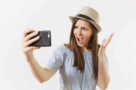 Irritated dissatisfied woman in blue dress, hat doing selfie shot on mobile phone or video call isolated on white background. People, sincere emotions, lifestyle concept. Advertising area. Copy space