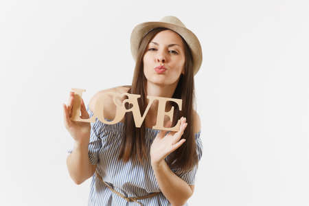 Young woman in blue dress, hat holding wooden word love isolated on white background. St. Valentine's, International Women's Day holiday. People, sincere emotions, lifestyle concept. Advertising area