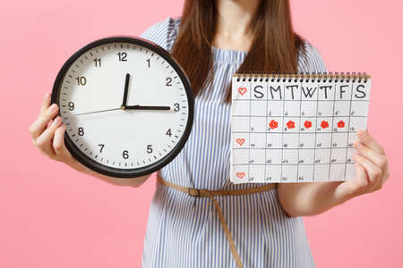 Cropped photo of woman in blue dress holding round clock, periods calendar for checking menstruation days isolated on trending pink background. Medical, healthcare, gynecological concept. Copy space Banque d'images - 104184696