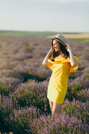 Portrait of young sensual beautiful woman in yellow dress on purple lavender flower blossom meadow field outdoors on summer nature background. Tender female near flowering bush. Lifestyle concept