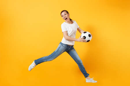 Young fun expressive European woman football fan jumping in air, cheer up support team, holding soccer ball isolated on yellow background. Sport, play football, cheer, fans people lifestyle concept Stock Photo