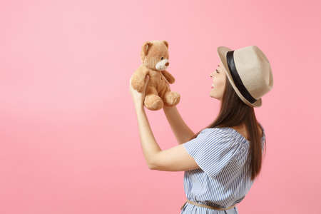 Portrait of young beautiful woman in blue dress, summer straw hat holding teddy bear plush toy isolated on pink background. People, sincere emotions, lifestyle concept. Advertising area. Copy space Banco de Imagens