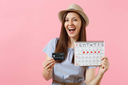 Portrait of happy woman in blue dress, hat holding credit card, periods calendar, checking menstruation days isolated on trending pink background. Medical healthcare gynecological concept. Copy space
