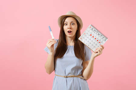 Shocked sad woman in blue dress, hat hold in hand pregnancy test, periods calendar for checking menstruation days isolated on pink background. Medical, healthcare, gynecological concept. Copy space