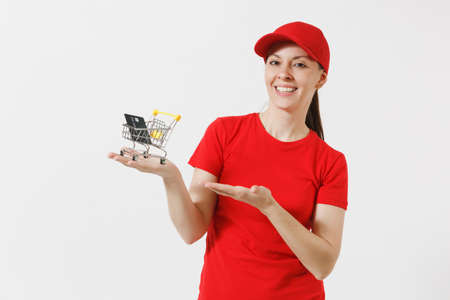 Delivery woman in red uniform isolated on white background. Female courier or dealer in cap, t-shirt holding supermarket grocery push cart for shopping, credit card. Copy space for advertisement