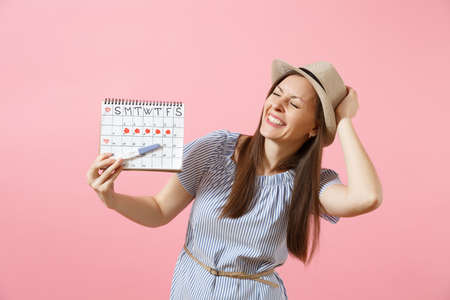 Excited happy woman in blue dress, hat hold in hand pregnancy test, periods calendar for checking menstruation days isolated on pink background. Medical, healthcare, gynecological concept. Copy space