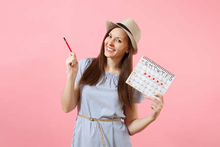 Portrait of young woman in blue dress, hat holding red pencil, female periods calendar for checking menstruation days isolated on pink background. Medical healthcare gynecological concept. Copy space
