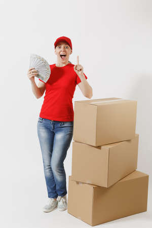 Full length of delivery woman in red cap, t-shirt isolated on white background. Female courier near empty cardboard boxes, bundle of dollars, cash money. Receiving package. Copy space advertisement