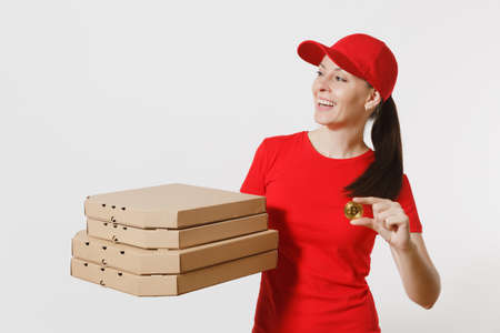 Delivery woman in red cap, t-shirt giving food order italian pizza in cardboard flatbox boxes isolated on white background. Female pizzaman working as courier holding bitcoin, coin of golden color Foto de archivo