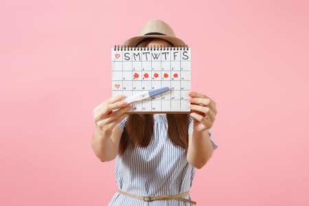 Podekscytowana szczęśliwa kobieta w niebieskiej sukience, trzymaj kapelusz w ręku, test ciążowy, kalendarz okresów do sprawdzania dni miesiączki na białym tle na różowym tle. Medycyna, opieka zdrowotna, koncepcja ginekologiczna. Skopiuj miejsce