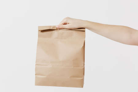 Close up female holds in hand brown clear empty blank craft paper bag for takeaway isolated on white background. Packaging template mockup. Delivery service concept. Copy space. Advertising area Stock Photo - 104187442