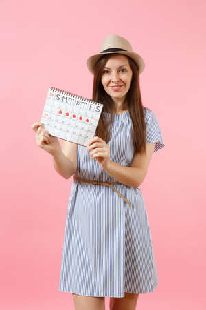 Portrait of young woman in blue dress, hat holding periods calendar for checking menstruation days isolated on bright trending pink background. Medical, healthcare, gynecological concept. Copy space Stock Photo